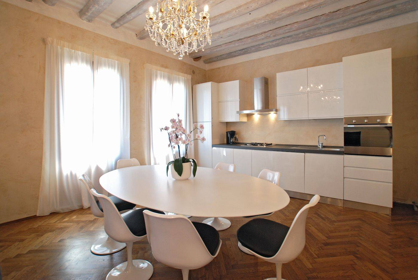 the kitchen is fully equipped and there is a large designer table with 8 chairs