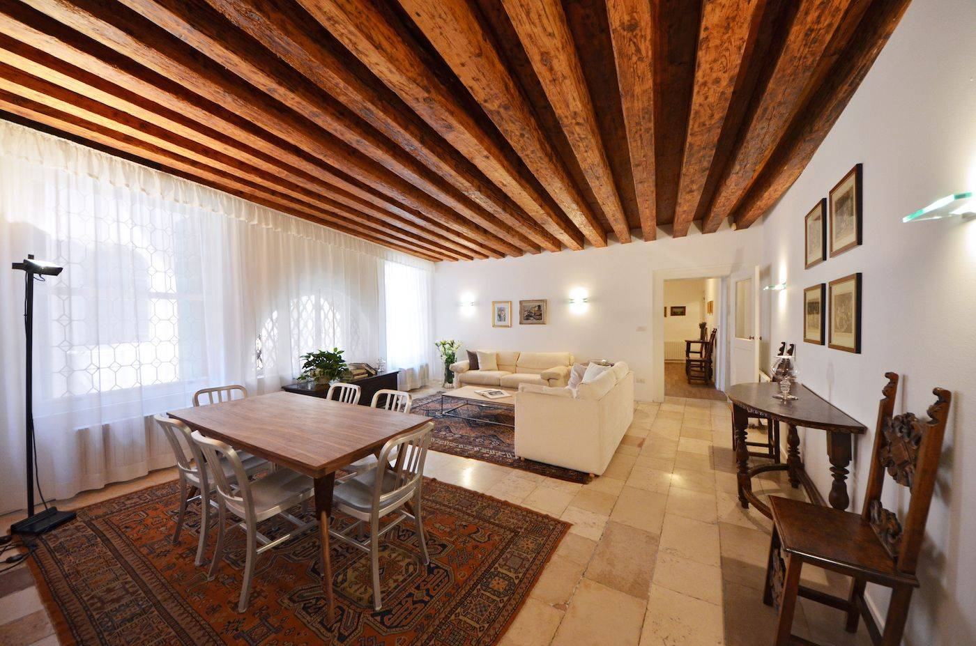 the spacious living room features beautiful wooden beams, antique terracotta flooring, large windows with canal view