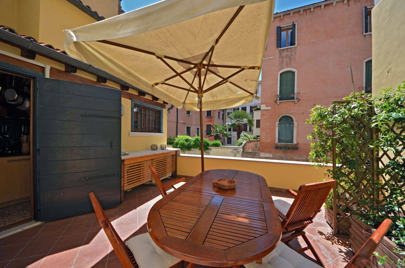 there is a table for up to 6 people and a large sun umbrella