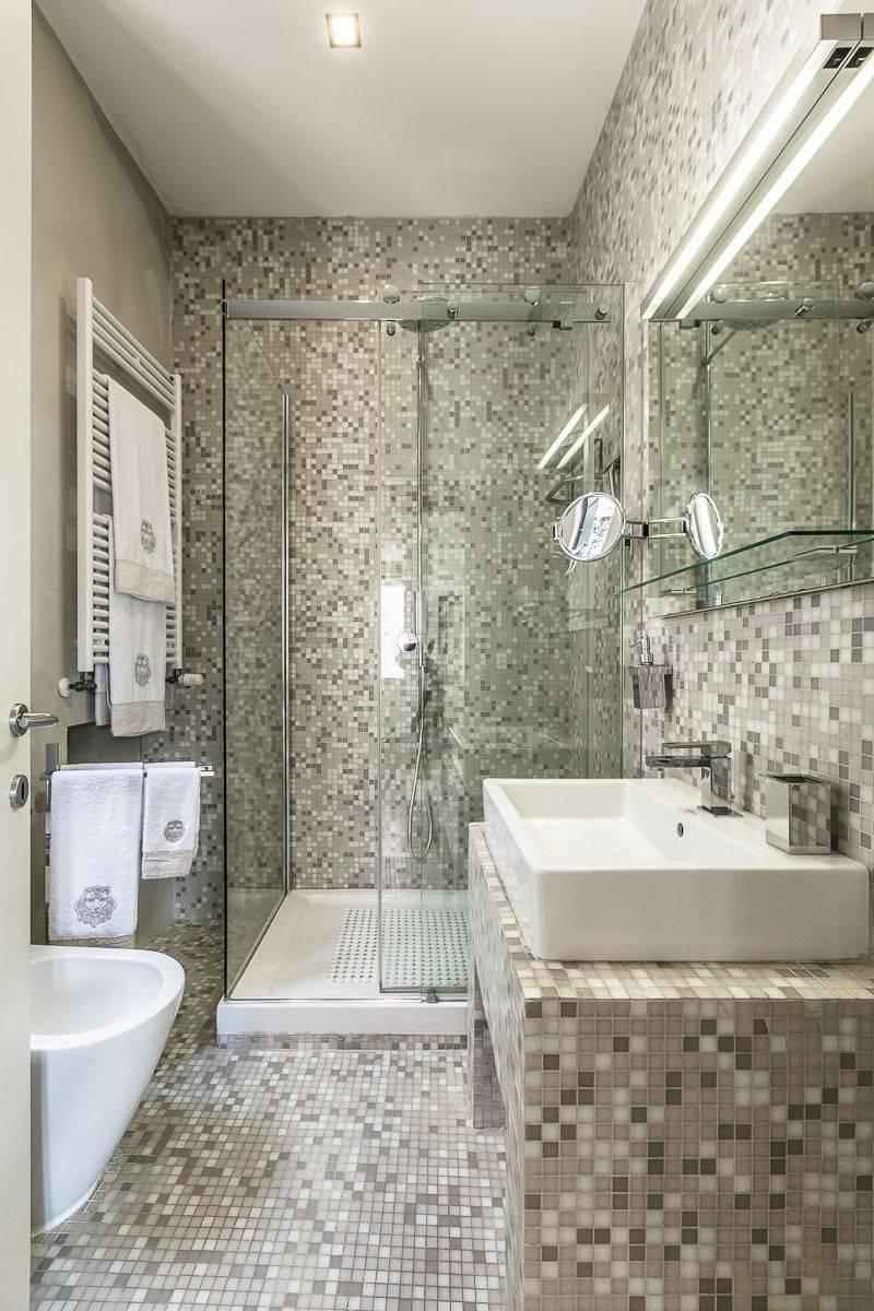 the mosaic en-suite bathroom features a luxurious shower cabin