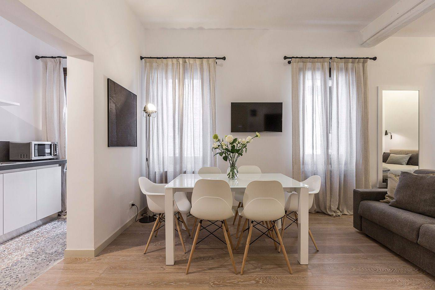 kitchen, dining table, sofa and bed are fitted with style in the studio