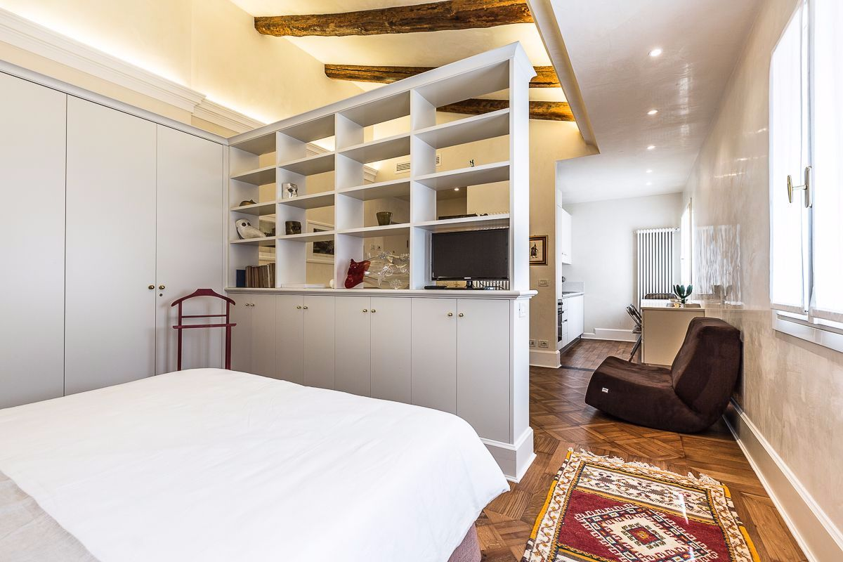 a library divides the bed from the sitting area