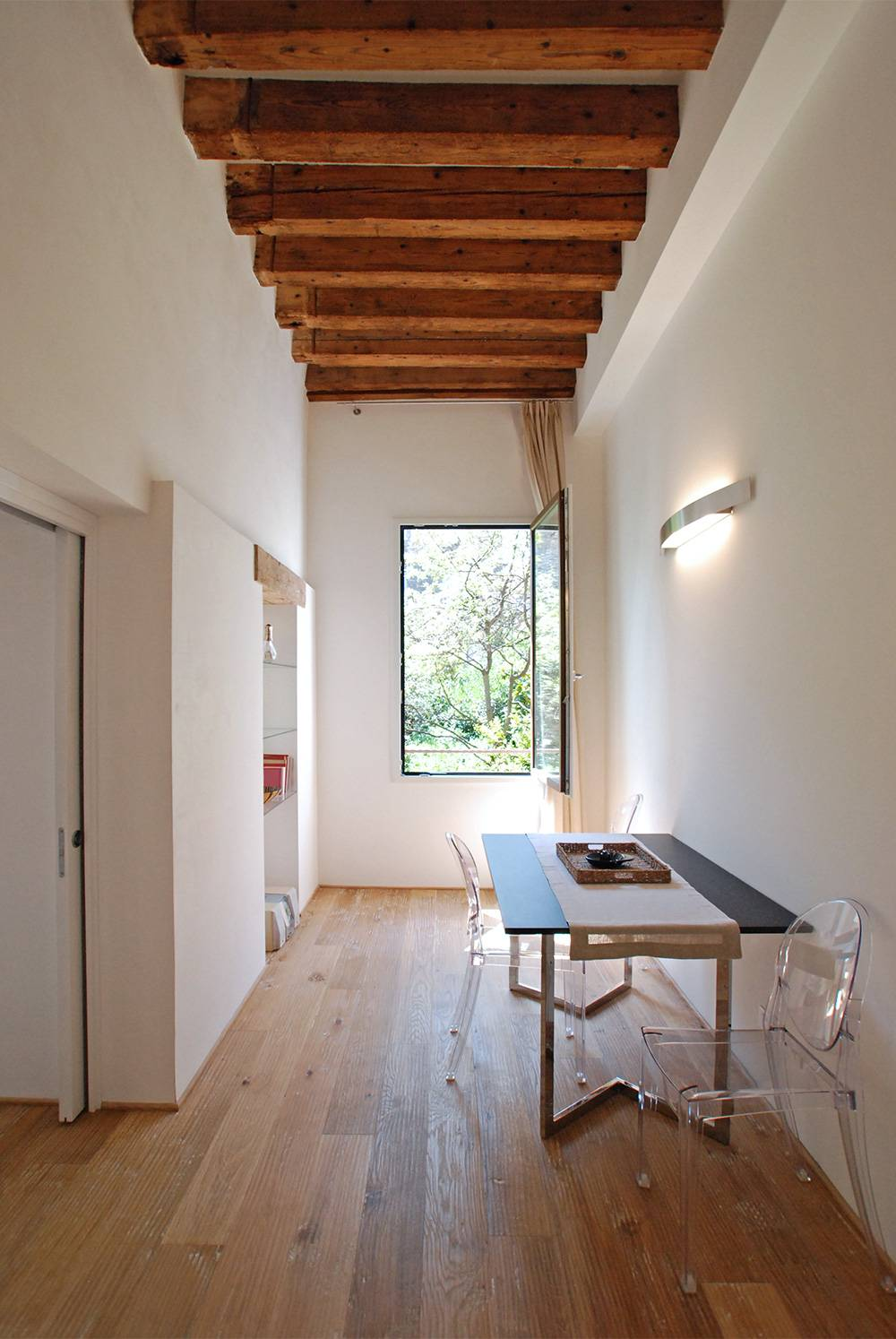 high ceilings with ancient wooden beams and brushed parquet flooring confer warmth to the ambience