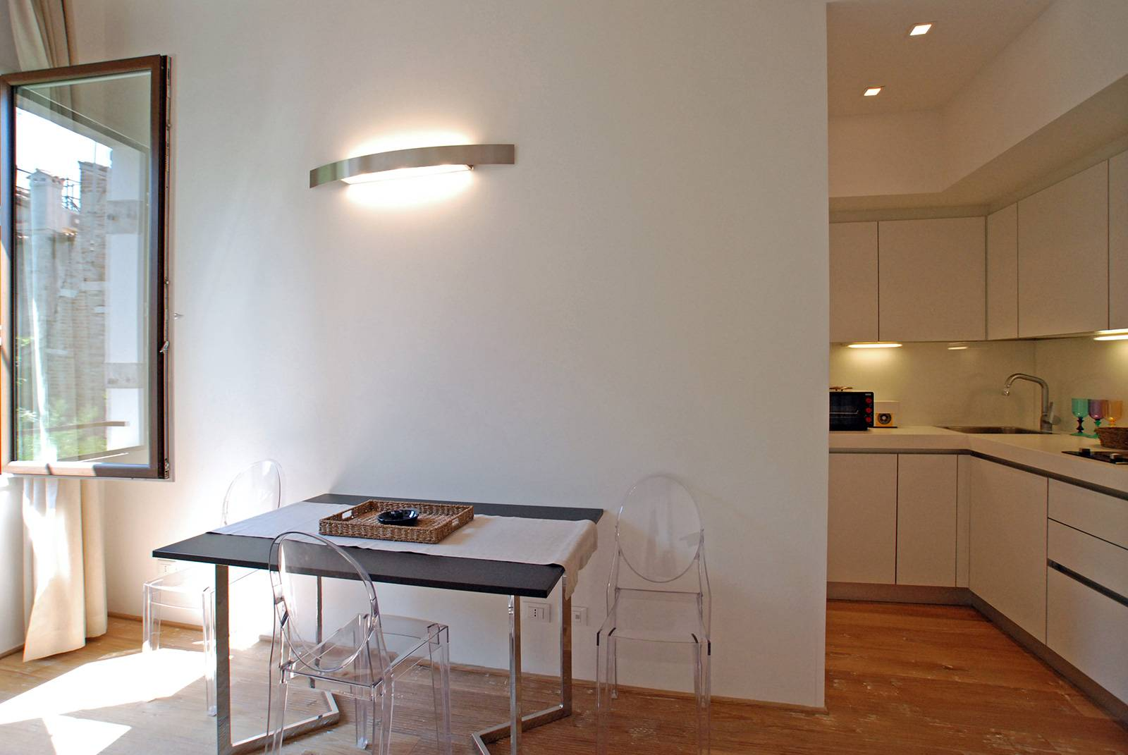 the living room has a table for 4 people and a functional kitchenette