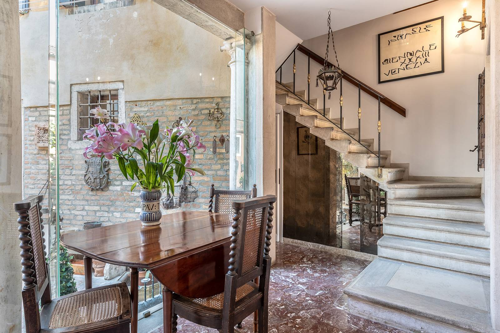 an elegant marble stairway leads to the 1st floor