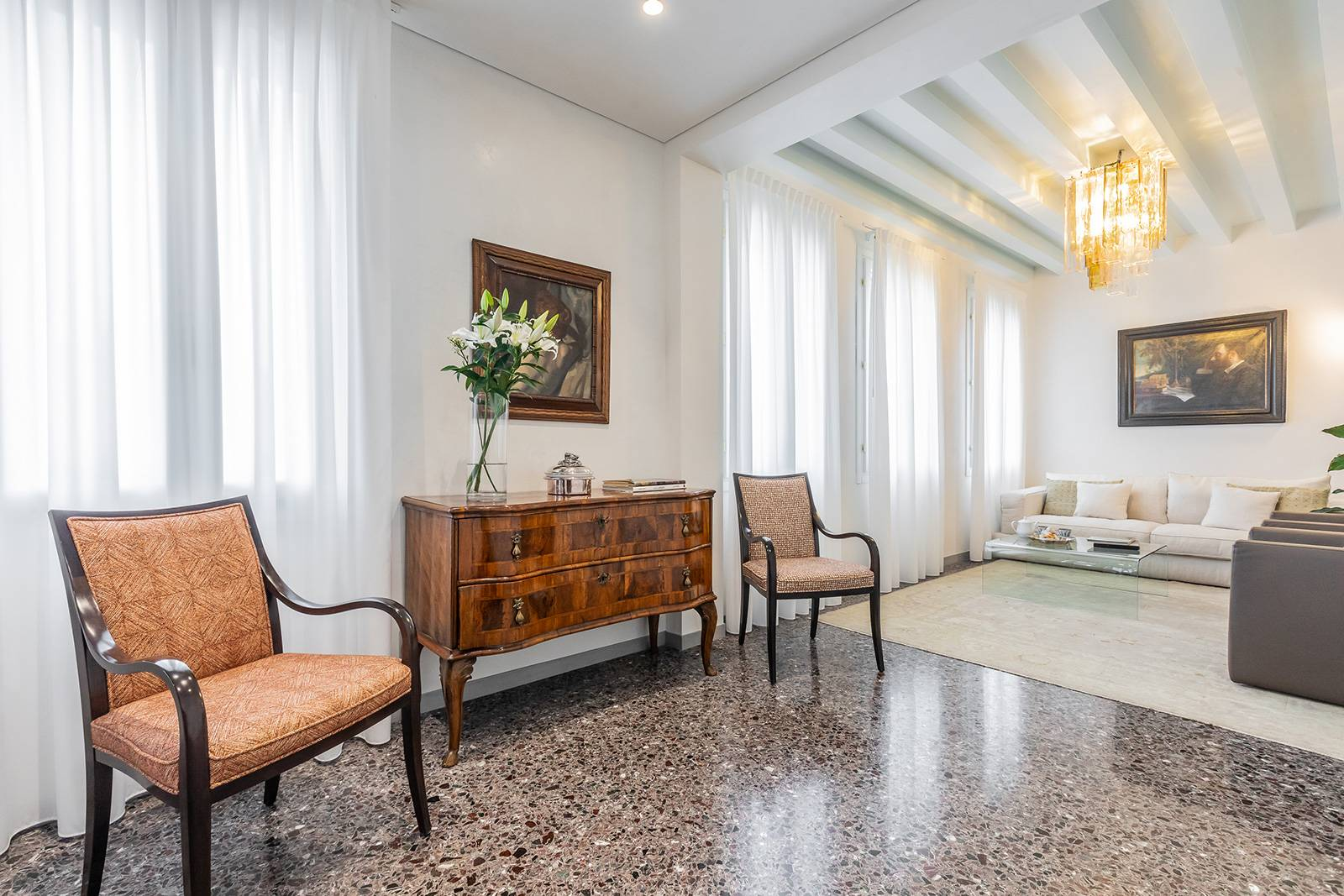 the beautiful Terrazzo Veneziano flooring and the antique wooden beamed ceiling perfectly blends with antique furniture
