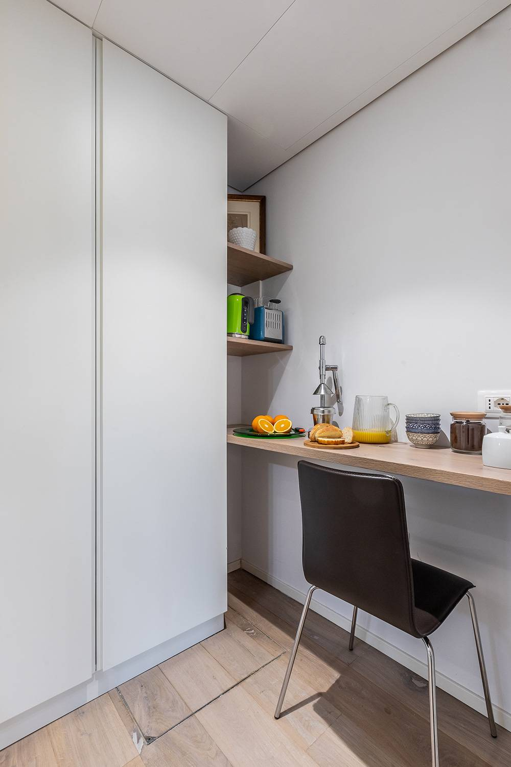there is a breakfast corner with kettle and toaster next to the closet