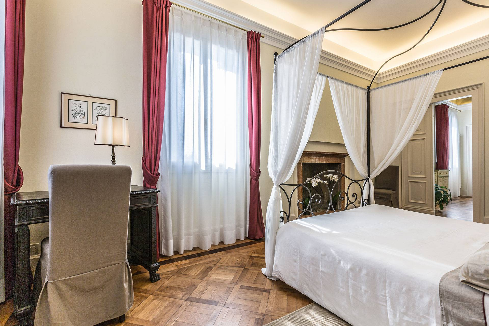 the master bedroom boasts a canopied bed dressed with nice linen
